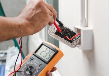 Electrician Is Using A Digital Meter To Measure The Voltage At T